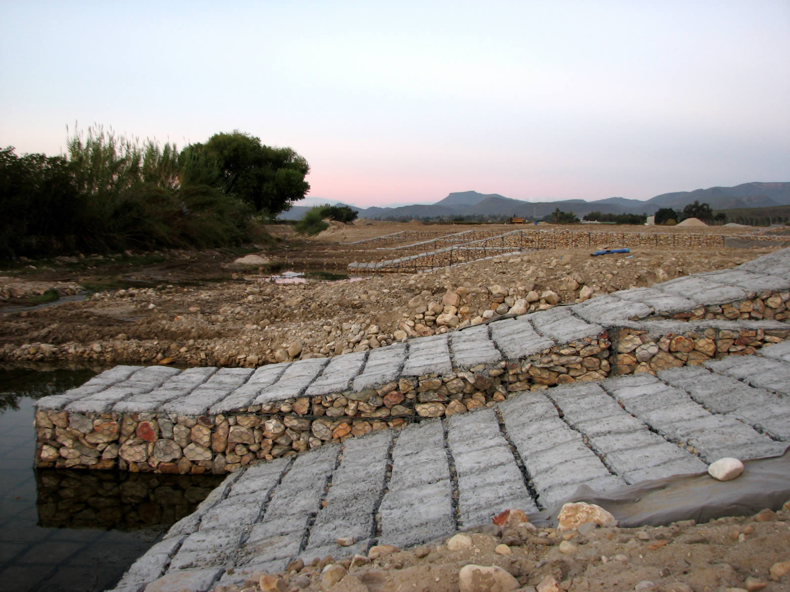 Gabion groynes with concrete panels to protect against abrasion