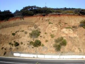 Heavily eroded cut slope posing a danger to passing traffic
