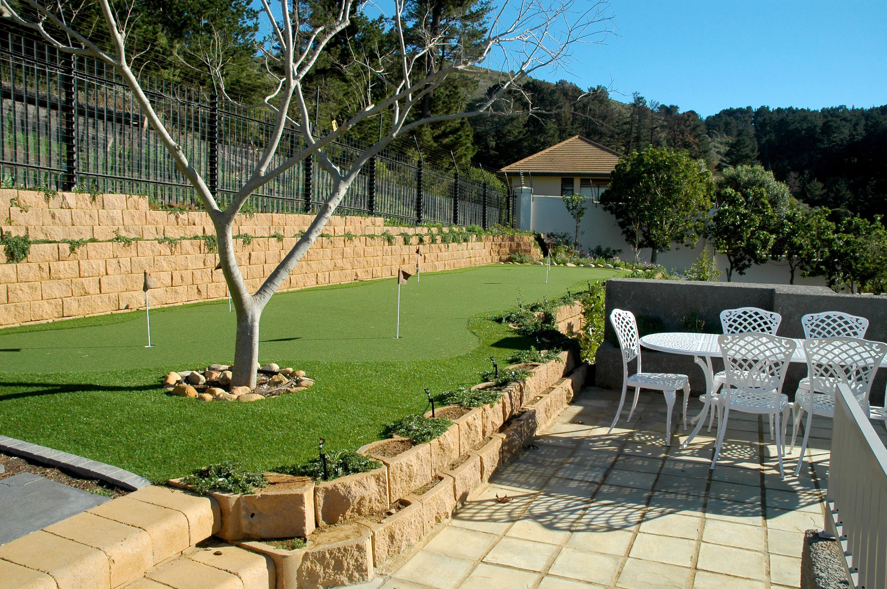 The retaining wall accommodates a small golf green