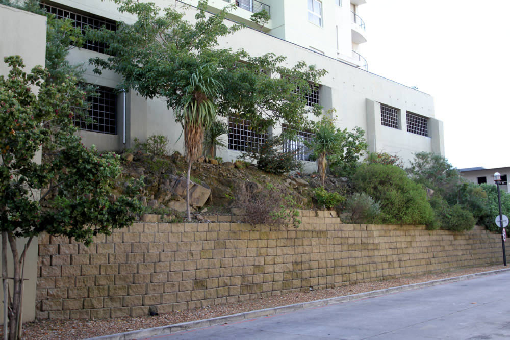Rock face retaining blocks lend a more earthy feel to the retaining wall