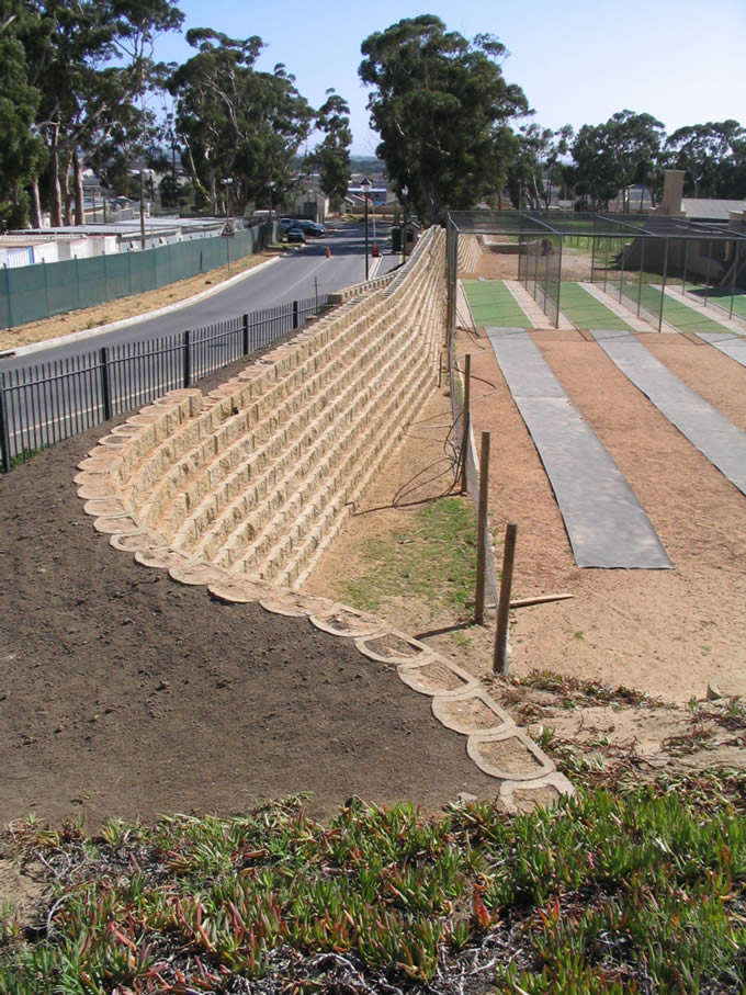 Walls are backed with an earth berm, level top and sloping away at 45º
