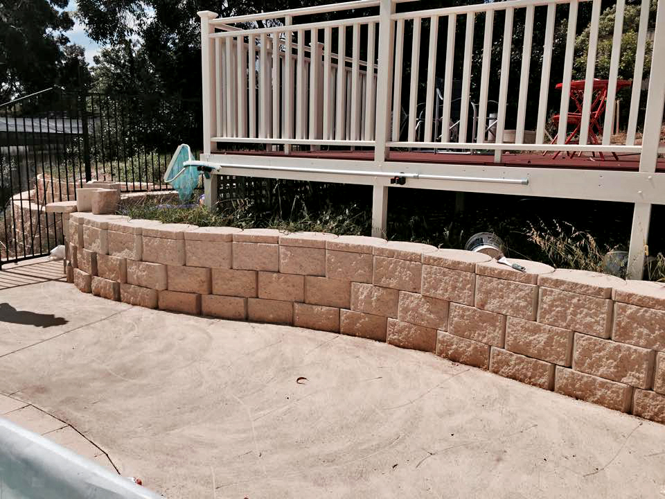 The wall runs along and next to the pool