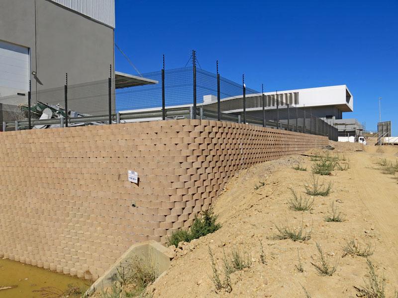 Terraforce retaining blocks lining a slope bordering a detention pond.