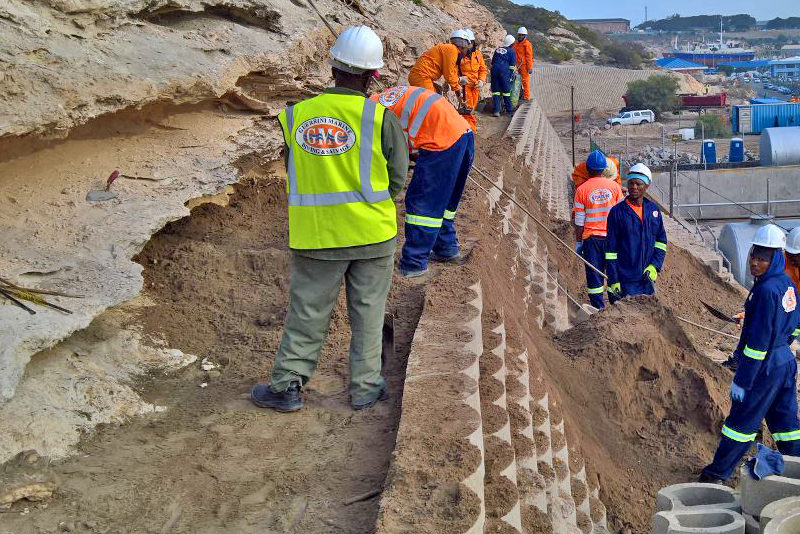 Retaining wall with cement stabilised back-fill