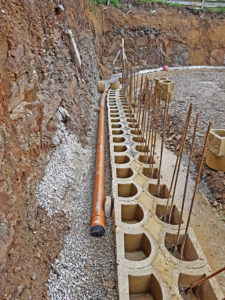 Foundation with protruding re-bars and first double layer of blocks installed with sub-soil drain