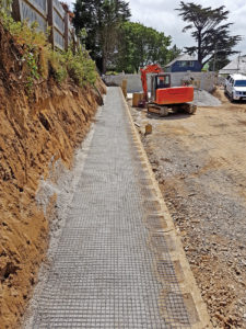 Backfill compacted with first layer of geo-grid rolled out.