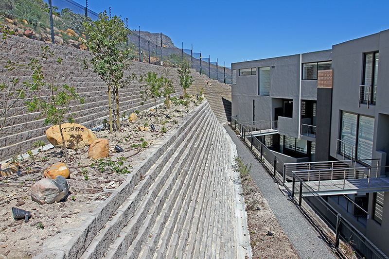 The wall retains a steep slope behind the luxury development