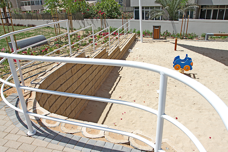 A railing add a finishing touch to the ramp leading down to the play area