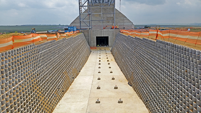 Cross contour cuttings to accommodate conveyor belt racks necessitated sloped retaining structures to protect the facings on both sides.