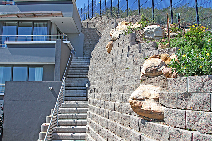 Fire escape staircase on the other side of the building with a rock worked into the wall