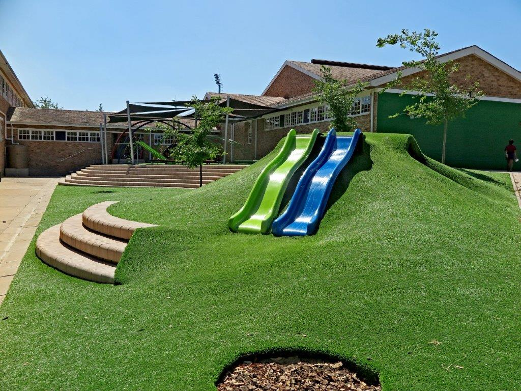 Instead of hard concrete paving, the space now features comfortable steps and seating, modern play equipment