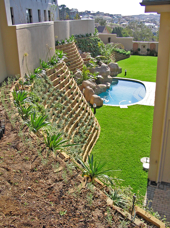 At Kanonberg Estate in the Western Cape, Terraforce L11 rock-face blocks provided a level, spacious platform -- about 3m above road level -- around a house built on a steeply sloping erf.  To soften the walls that support the fill for this platform, various flowerbeds and steps were added into the design.