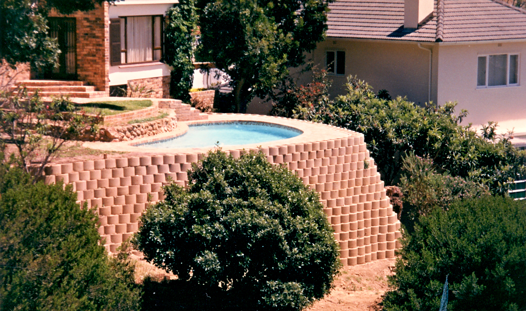 Pool in Cape Town, founded at ground level, in small sloping garden. The wall foundations, situated on a steep slope, were reinforced, spanning between 1m x 1m x 2m deep mass foundations. these in turn were tied back to concrete anchors (called a dead man anchor) placed underneath the RC pool.